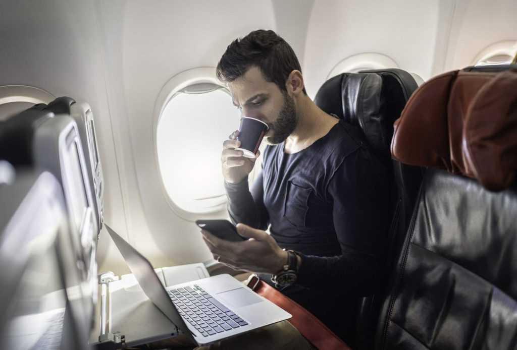 Man working in airplane using cellphone and drinking coffee
